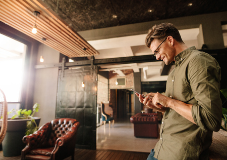 Side view of handsome young man reading text message on his mobile phone and smiling. Creative businessman using cell phone during break.