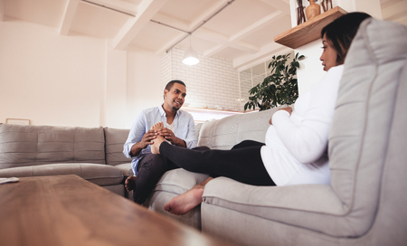 Husband massaging his pregnant wife legs while sitting together on sofa. Man giving feet massage to pregnant woman at home. Stock Photo