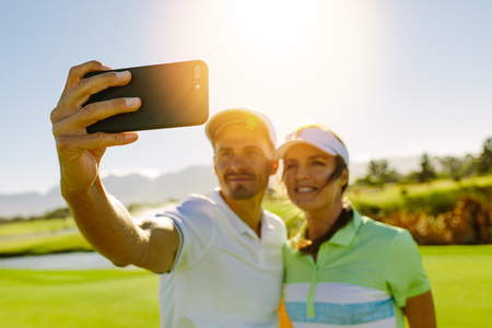 Young couple taking self portrait at golf course. Male and female golfers taking selfie with smart phone at field on sunny day.
