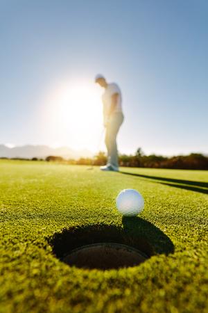 Pionowe ujęcie profesjonalnego golfisty wprowadzenie piłeczki do golfa w otworze. Piłeczka golfowa przy dołku z graczem w tle w słoneczny dzień.
