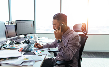 Businessman talking on mobile phone and making notes. Man sitting at his office desk working on graphs and charts and discussing on phone. Archivio Fotografico