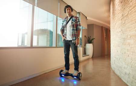 Full length shot of stylish young man riding on electrical self-balancing scooter in modern office corridor.