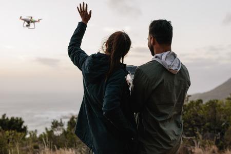 飛行ドローンと農村と話して自己写真で一緒に立っている若いカップルの屋外撮影。 写真素材