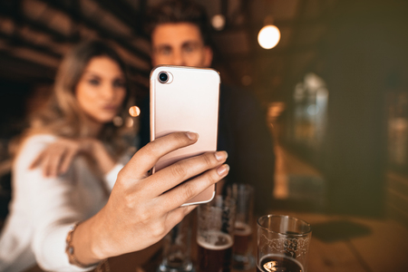 Close up of couple sitting in the bar and taking a selfie with smart phone. Focus on mobile phone in hand of woman. Stock Photo