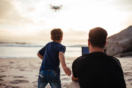 Rear view of young man operating the drone by remote control at the beach and son running. Young man with little boy enjoying summer vacation. Stok Fotoğraf
