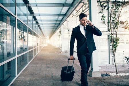 Hübscher junger Mann auf Geschäftsreise gehend mit seinem Gepäck und auf Mobiltelefon am Flughafen sprechen. Reisender Geschäftsmann, der Anruf tätigt.