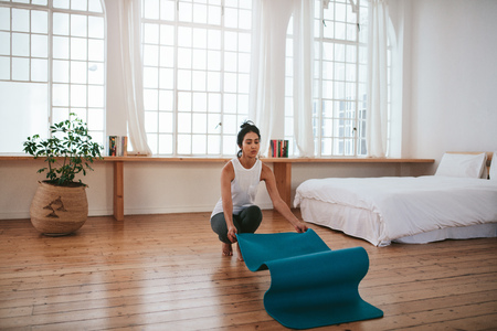 Indoor shot of fit young woman putting yoga mat on floor. Fitness female about to start the yoga workout on floor at home. Stock Photo