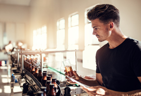 Young man examining the quality of beer at brewery. Male inspector working at alcohol manufacturing factory checking the craft beer. Archivio Fotografico