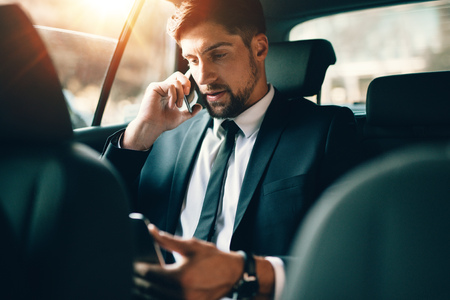 Young businessman talking on mobile phone and using tablet pc while sitting on back seat of a car. Caucasian male business executive travelling by a taxi and looking at digital tablet. Фото со стока