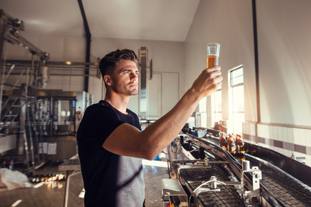若い男のクラフト ビール醸造所での品質を調べること。ビールをチェック アルコール製造工場で働いて男性警部。