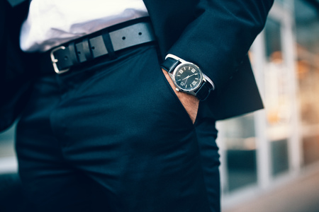 Close up of a business mans hand wearing a watch. Hand in pocket with wrist watch.