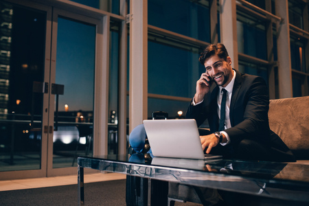 Smiling businessman with laptop talking on cellphone at the airport waiting lounge. Handsome man at waiting room in airport terminal.