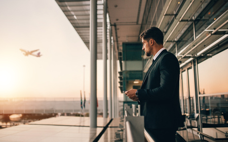 Airport lounge balcony and looking at airplane take off. Business man waiting for his flight. Stock Photo