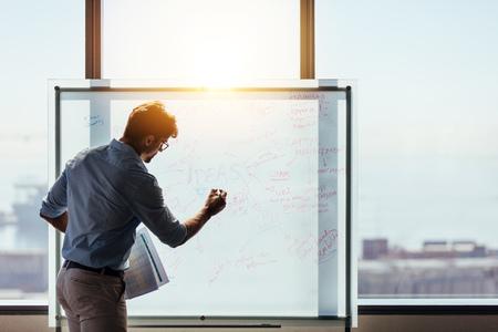 Zakenman die een presentatie maakt op kantoor. Ondernemer die whiteboard gebruikt om ideeën voor bedrijfsplanning en besluitvorming te presenteren. Stockfoto - 81446742