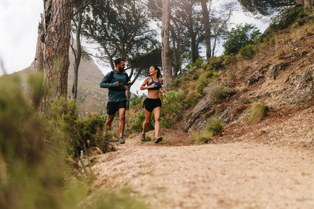 Full length portrait of young man and woman running on country path. Young couple on cross country run in morning.