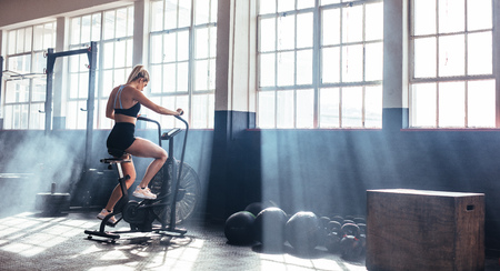 Female working out on fitness at the gym. Woman training on exercising bike at gym. Imagens