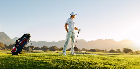 해질녘에 골프 코스에 서서 멀리보고 젊은 남자의 전체 길이. 전문 남성 골퍼 필드에 골프 클럽을 들고입니다. 스톡 콘텐츠 - 81481141