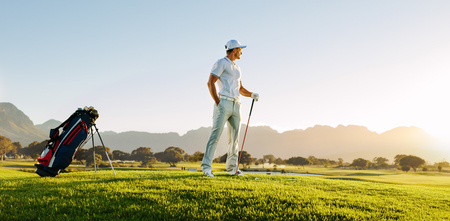 Full length of young man standing on golf course at sunset and looking away. Professional male golfer holding golf club on field.