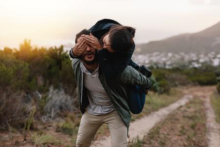 Ritratto di giovane uomo che porta la donna sulla schiena, con la donna che copre gli occhi dell'uomo. Giovani coppie allegre che si divertono nella campagna. Archivio Fotografico - 81481142