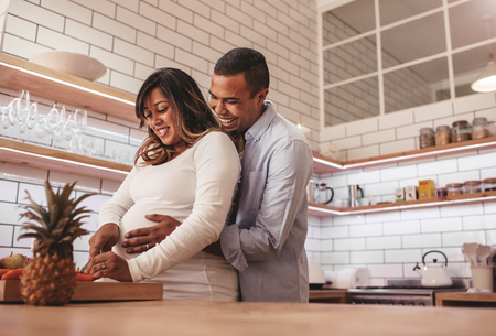 Young couple cooking together in the kitchen while man embracing his pregnant wife. Happy young couple cooking food at home, chopping vegetable on kitchen counter. Stok Fotoğraf