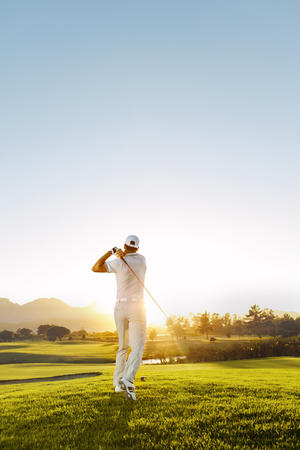 Rear view of golfer hitting driver on a golf course in the sun. Full length shot of young man playing golf on a sunny day.