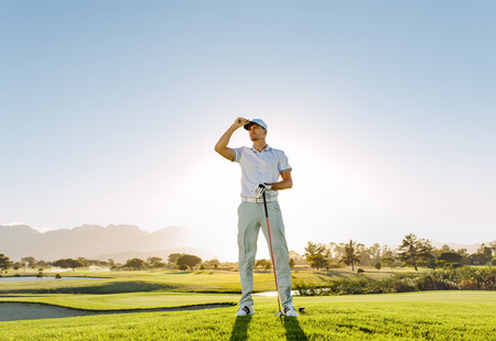 Full length of young caucasian man standing on golf course on a summer day and looking away. Male golfer holding golf club on field.