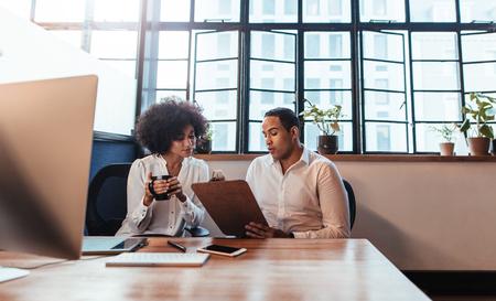 2 つの若い起業家のオフィスの机で一緒に座っての撮影。男は事務所で女性にクリップボードに何かを示します。
