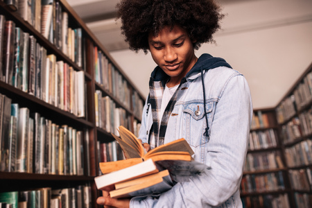 African male college student standing in library with lots of books. University student looking for study references. Banque d'images