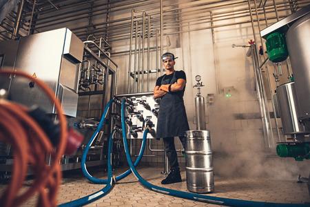 Überzeugter Brauer im Schutzblech mit den Armen kreuzte das Betrachten der Kamera bei der Stellung vor industriellen Ausrüstungen an der Brauereifabrik. Schuss in voller Länge des jungen Mannes in der schützenden Arbeitskleidung, die an der Brauerei steht.