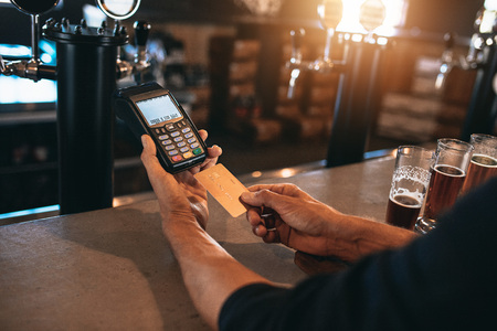 Cropped image of man paying using a credit card at bar. Man at brewery factory with varieties of beers on counter.