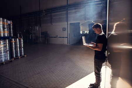 Horizontal shot of young man standing in brewery factory working on laptop. Brewery factory owner using laptop.