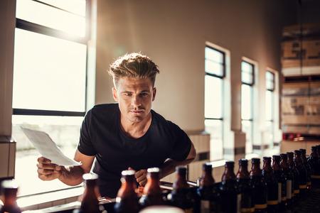 맥주의 품질을 검사하는 양조 공장 노동자. 맥주 병을 검사하는 알코올 제조 공장에서 작동하는 젊은 남자 관리자.