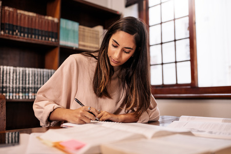 Young student making notes in the library. College female student preparing for the exam while sitting in library. Stok Fotoğraf