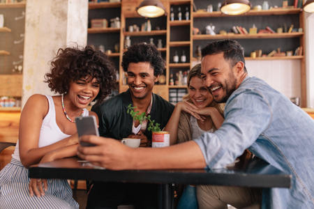Group of young people sitting in a cafe and looking at the photos on smart phone. Young men and women sitting at cafe table and using cell phone. Stock Photo