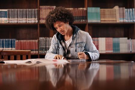 Jonge afro Amerikaanse man zittend aan tafel met boeken voor het vinden van informatie in de bibliotheek. Jonge student die nota's van boeken voor studie in bibliotheek maakt. Stockfoto