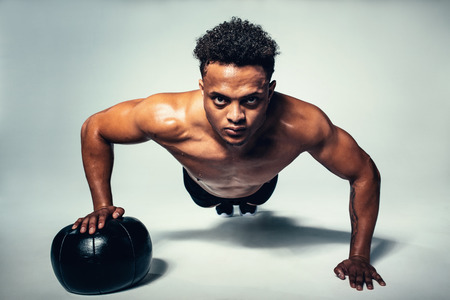 Shot of muscular young man doing push up on medicine ball. Fitness male working out with a medicine ball on grey background.