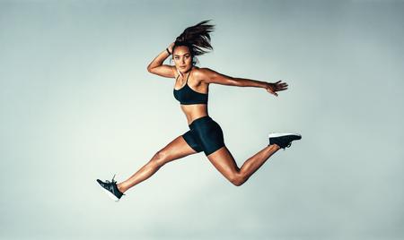 Studio opname van een sportieve jonge vrouw springen op grijze achtergrond. Mooi vrouwelijk model in sportkleding draagt in de lucht.