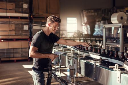 양조장에서 맥주 생산을 감독하는 젊은 남자. 알코올 제조 공장에서 일하는 사람. 그의 병에 담은 기계 근처에 서있다.