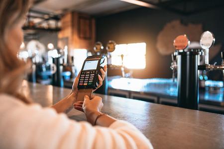 女性のクレジット カードを使用して請求書の支払いのショットをトリミング バー。キャッシュレス支払いを行う醸造工場で女性。