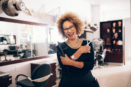 Smiling female hairdresser holding a hair straightener and scissors. Well equipped beauty salon with professional hairdresser. Zdjęcie Seryjne - 82107864