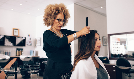 Female hair stylist working on a woman 's hair. Woman hairdresser serving her customer at the salon.