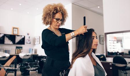 Weiblicher Friseur, der an dem Haar einer Frau arbeitet. Frauenfriseur, der ihren Kunden am Salon dient. Standard-Bild