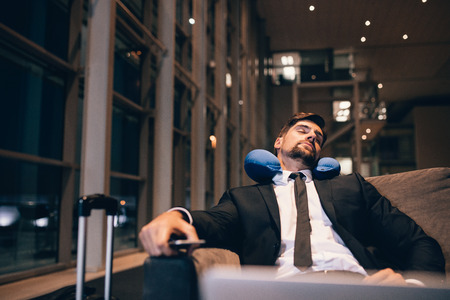 Traveler waiting at airport after flights delays and cancellations. Businessman asleep in airport lounge. Foto de archivo