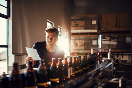 Young man supervising the process of beer manufacturing on brewery factory. Factory worker checking the process on the production line in brewery. Stock Photo