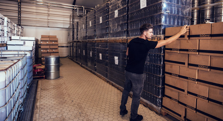 Young businessman looking at the packaged beer boxes in warehouse. Brewery owner verifying the beer boxes in delivery storage area.
