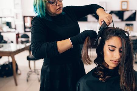 여자 살롱에서 머리를 점점입니다. 헤어 컬링 아이언을 사용하여 곱슬 머리에 직선 머리카락을 돌리는 헤어 스타일리스트.
