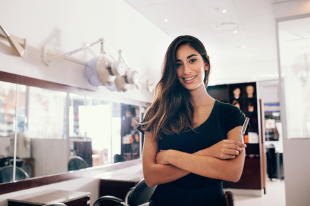 Professional woman hairdresser in salon with scissors in hand. Smiling young woman standing in salon with folded hands.