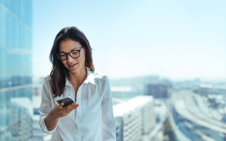 Businesswoman sending text messages using mobile phone. Young woman standing in her office in a highrise building overlooking the cityscape.