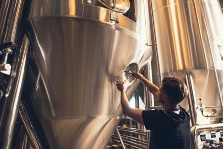 ビール製造工場で働く若い男。ビール醸造所に装置を操作します。