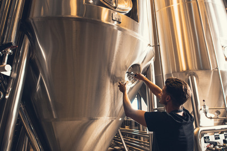 Young man working in beer manufacturing factory. Brewer working with industrial equipment at the brewery.